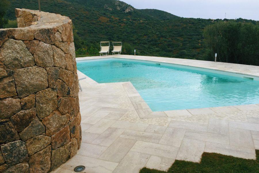 Gli antichi nuraghi ispirano la doccia elicoidale a bordo piscina per un outdoor esclusivo